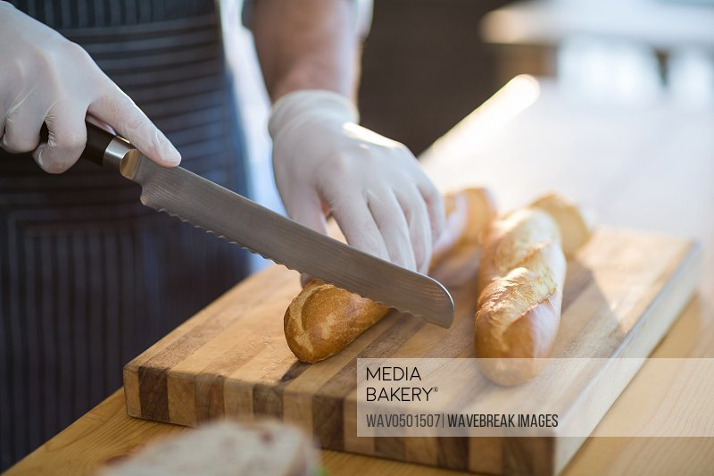 Mid-section of waiter chopping bread roll on chopping board in cafA?