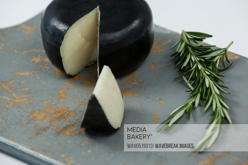 Black cheese with rosemary on chopping board