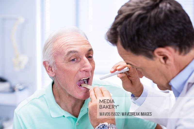 Doctor examining senior patients mouth