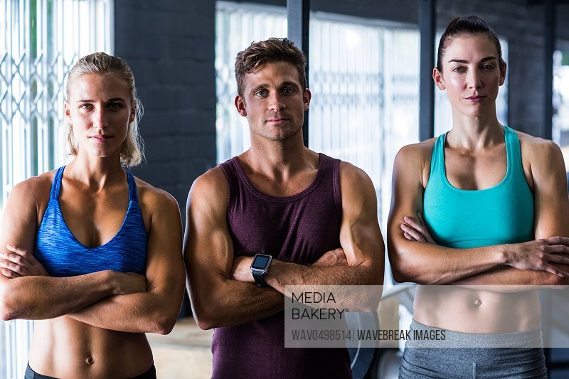Portrait of confident friends with arms crossed while standing in gym