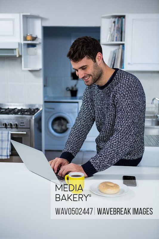 Man using laptop in the kitchen at home