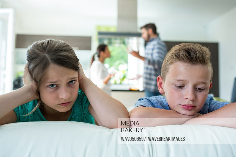 Sad kids leaning on sofa while parents arguing in background at home
