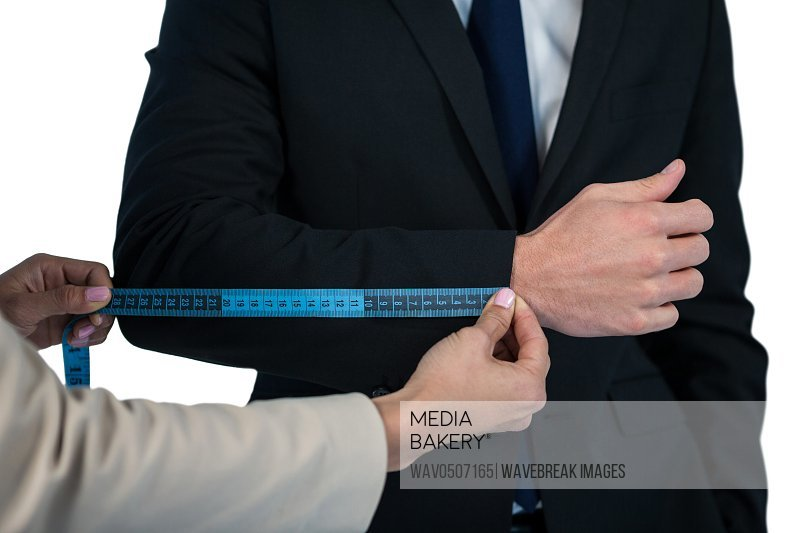 Mid section of businesswoman measuring businessman sleeve against white background