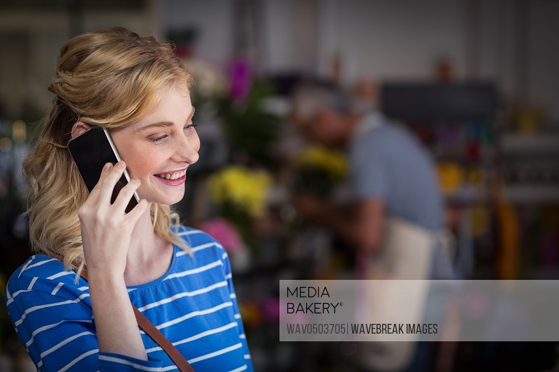 Smiling woman talking on mobile phone in flower shop