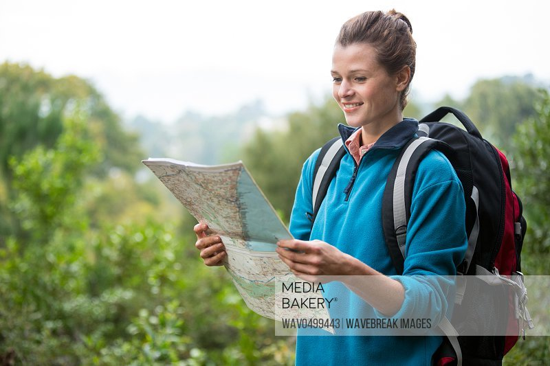 Smiling female hiker looking at map in forest
