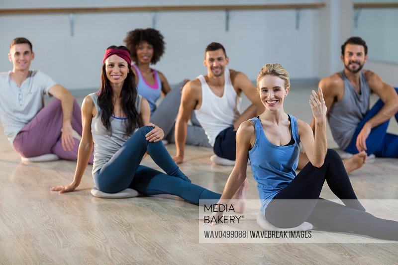 Portrait of group of people performing yoga in fitness studio