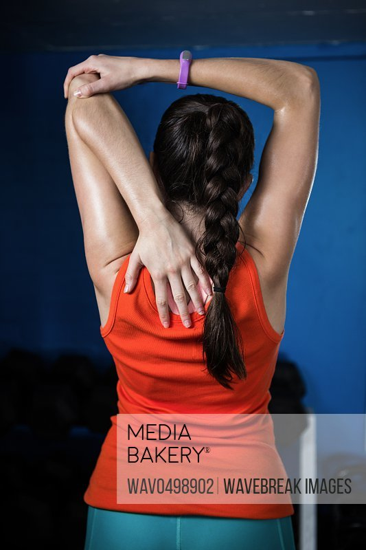 Rear view of female athlete exercising in gym