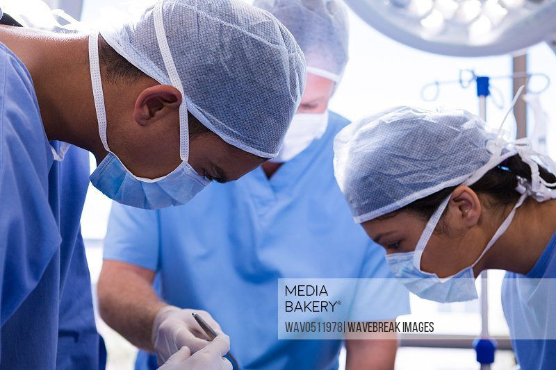 Group of surgeons performing operation in operation room at hospital
