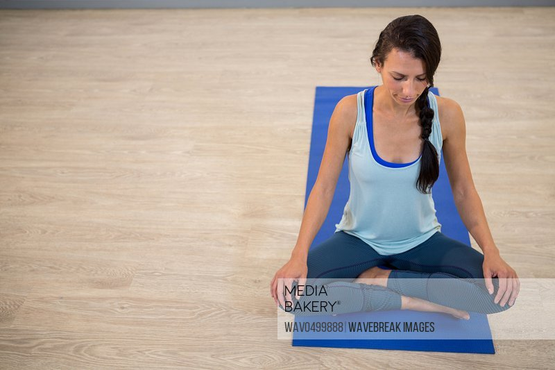 Woman meditating on exercise mat in gym