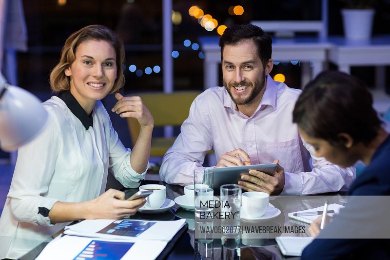 Businessman and businesswoman smiling while working in office at night