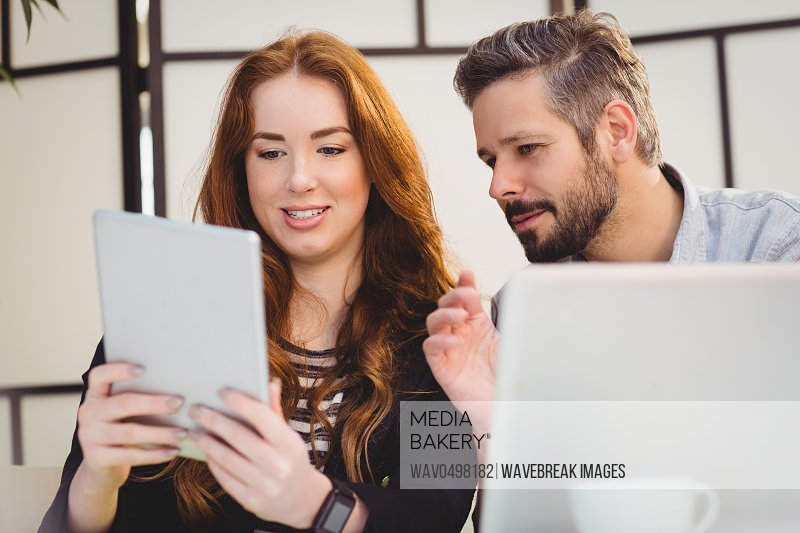 Attractive businesswoman with coworker using laptop in creative office