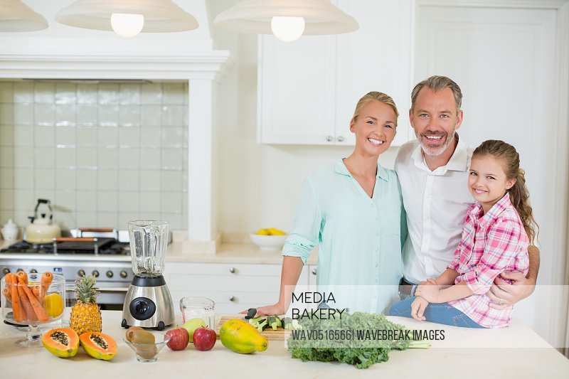 Portrait of parents with her daughter in kitchen