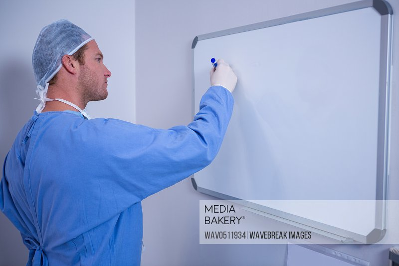 Male surgeon writing on whiteboard in hospital