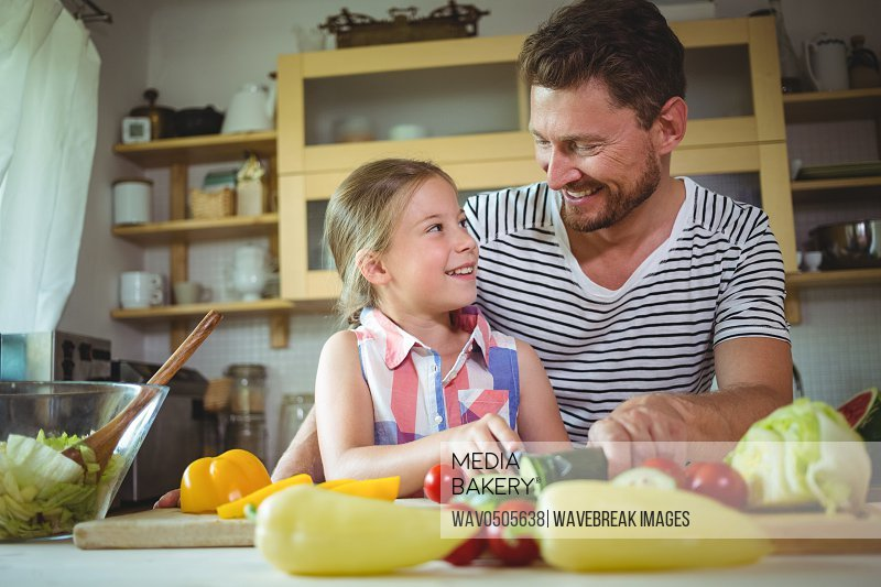 Father and daughter smiling at each other while preparing salad in the kitchen