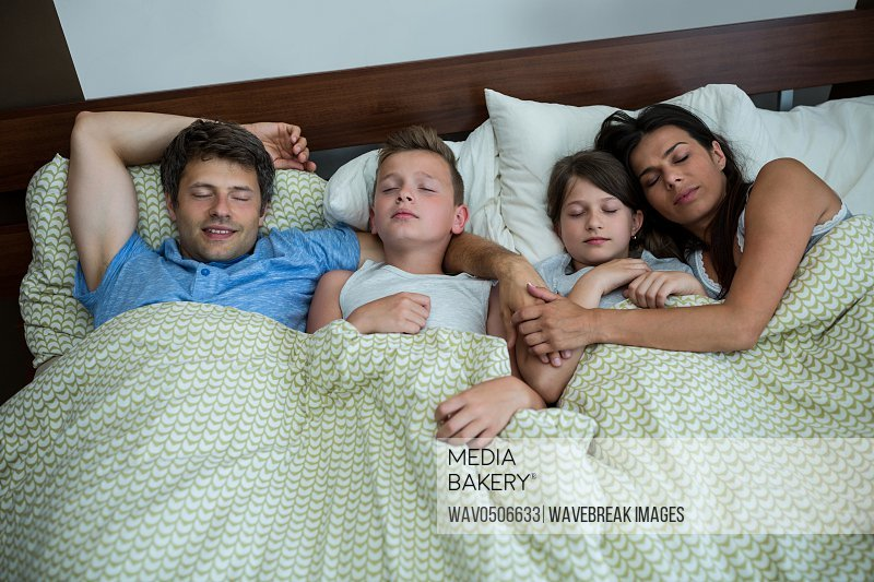 Family sleeping together in bedroom at home