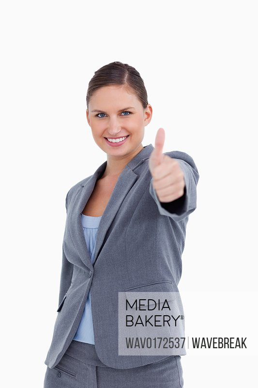 Smiling saleswoman giving her approval against a white background