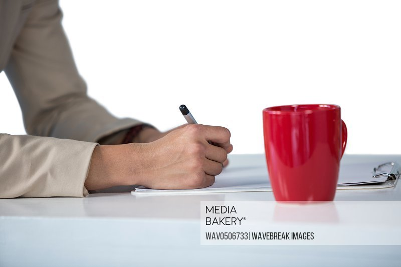 Businesswoman writing on clipboard with coffee mug on desk against white background