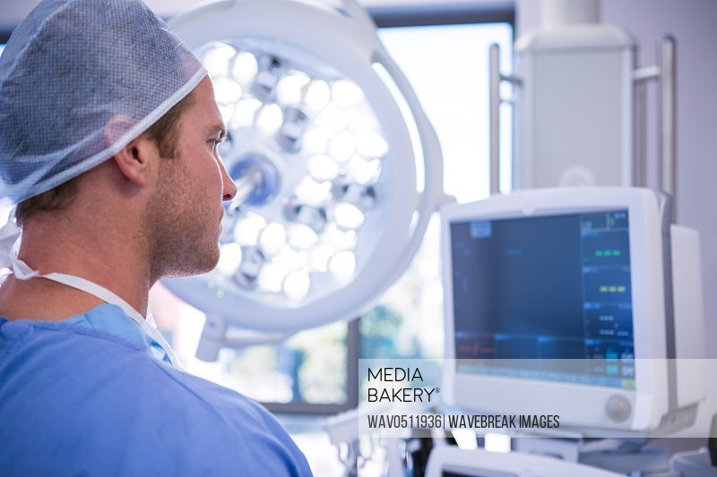 Male surgeon looking at patient monitoring machine in operation theater at hospital