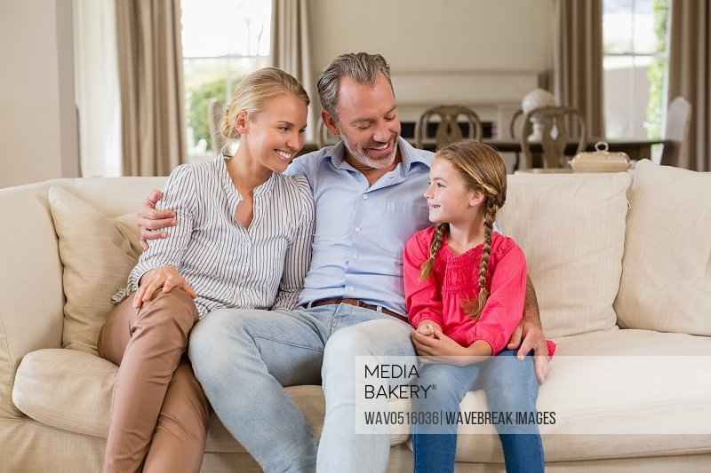 Parents and kids sitting on sofa in living room