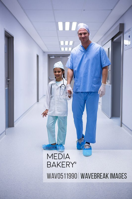 Portrait of doctor and girl standing in corridor at hospital