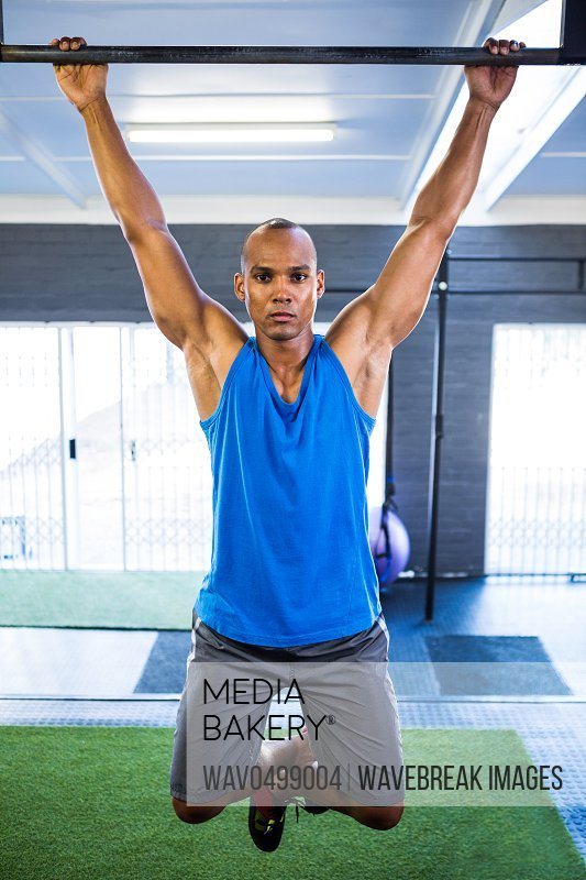 Portrait of male athlete doing chin-ups in gym