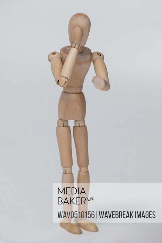 Wooden figurine standing and pretending to talk on phone against white background