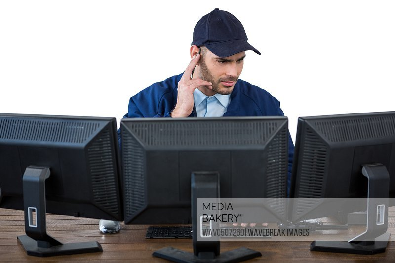Security officer listening to earpiece while using computer against white background