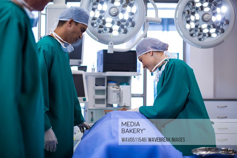 Surgeons performing operation in operation theater of hospital