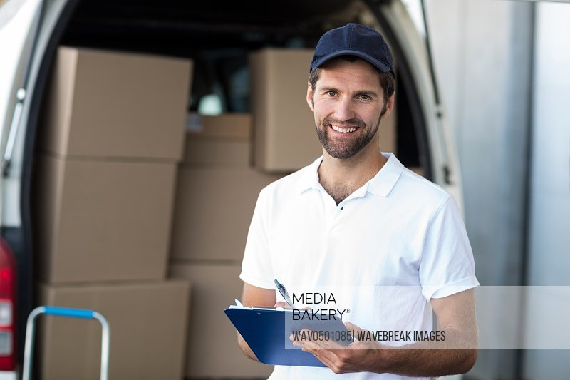 Portrait of delivery man holding a clipboard in front of van outside the warehouse