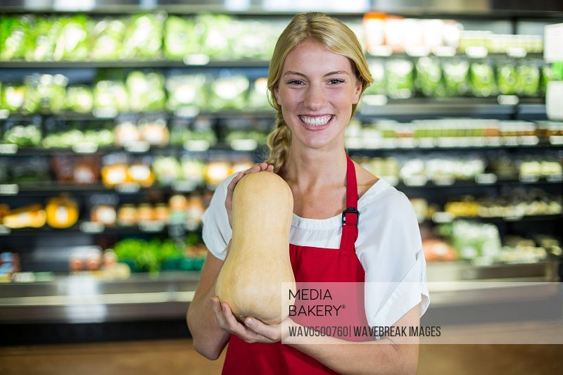 Smiling female staff holding a vegetable in organic section