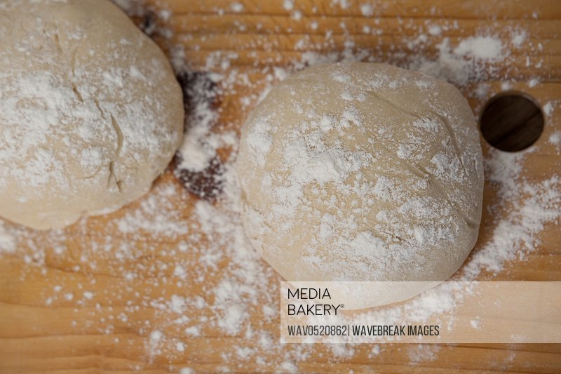 Pizza dough and flour on chopping board