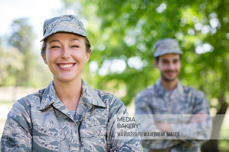 Portrait of a military couple standing with arms crossed in park