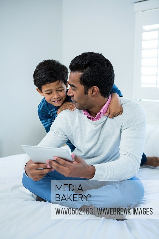 Father showing digital tablet to son on the bed in the bedroom