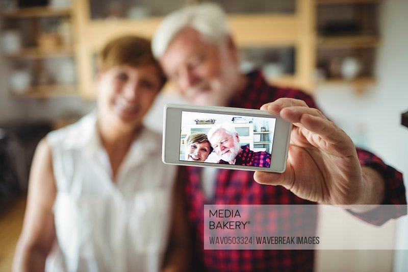 Senior couple clicking a picture on mobile phone in kitchen
