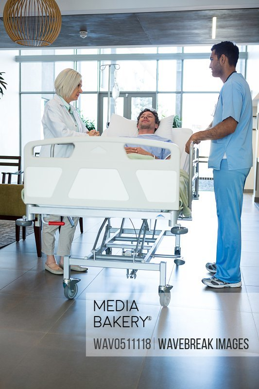Doctors interacting while patient lying on emergency stretcher in hospital