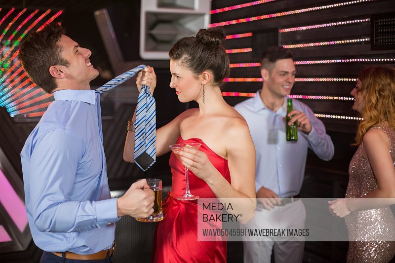 Couple having fun while having glass of beer and cocktail at bar