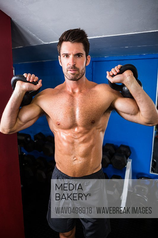 Portrait of shirtless athlete holding kettlebells while standing in gym
