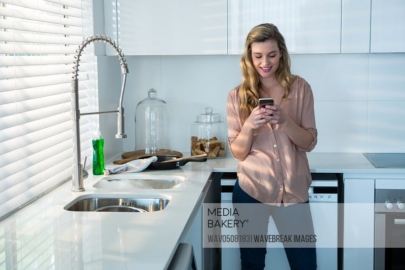 Woman using mobile phone in kitchen at home
