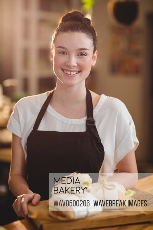 Portrait of smiling waitress holding a tray with sandwiches in cafe