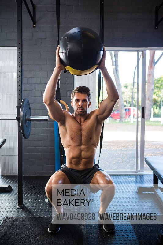 Full length of shirtless young man exercising with ball in gym