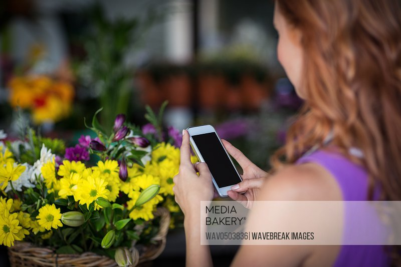 Female florist with phone taking the photo of yellow flowers in the flower shop