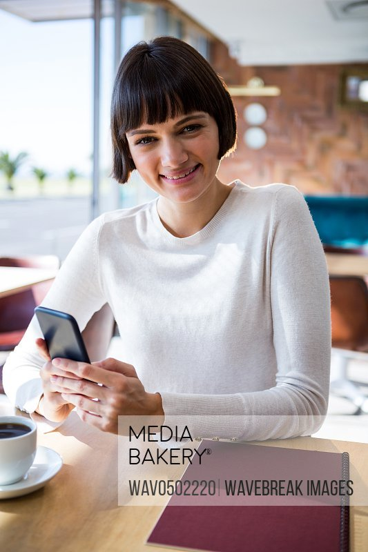 Portrait of smiling woman using mobile phone in cafeteria