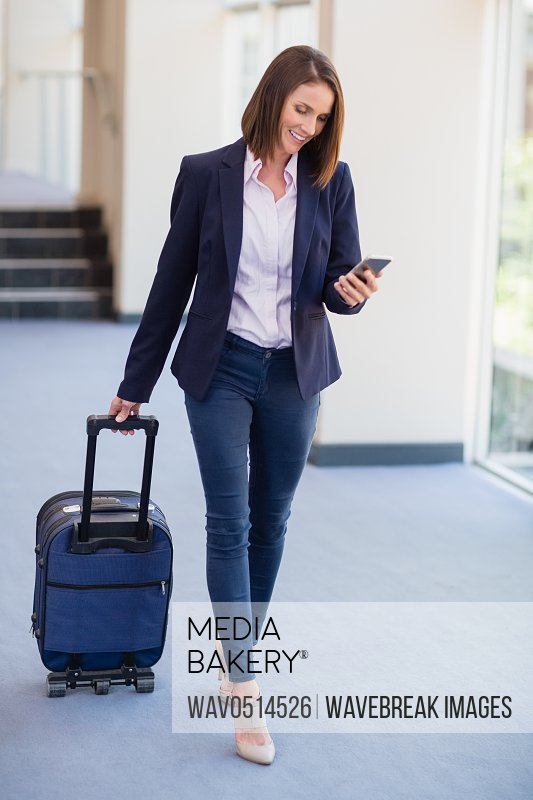 Businesswoman carrying luggage and using mobile phone