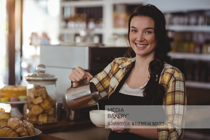 Portrait of waitress making cup of coffee at counter in cafe