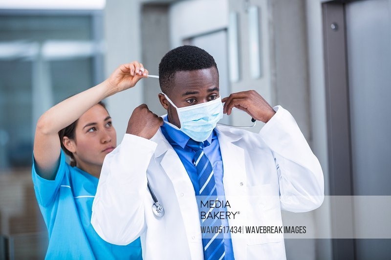Nurse helping doctor to put on surgical mask