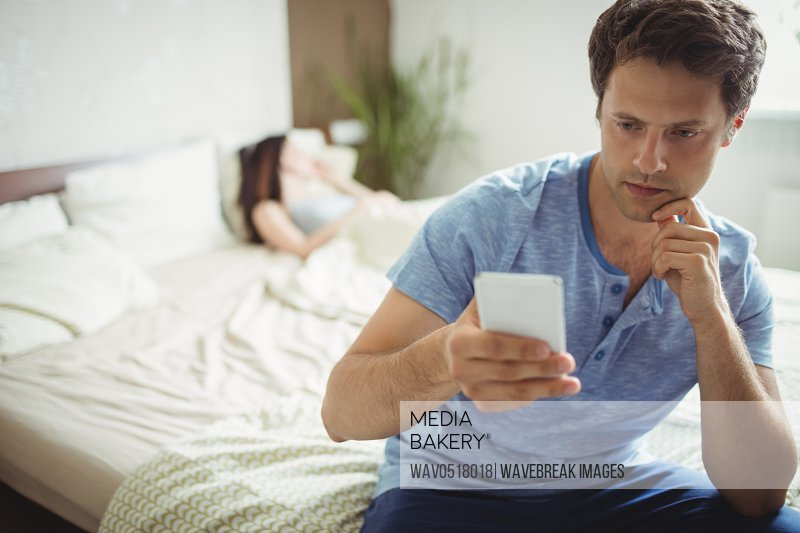 Man using mobile phone while woman sleeping on bed