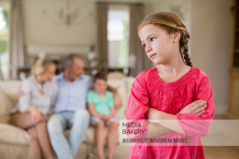 Thoughtful girl standing with arm crossed in living room