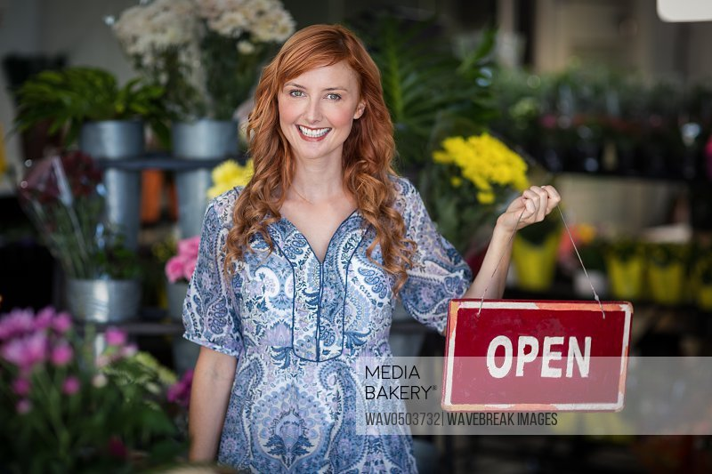 Portrait of smiling florists holding open sign placard in flower shop