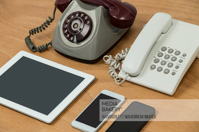 Close-up of vintage telephone, modern telephone, digital tablet and mobile phones