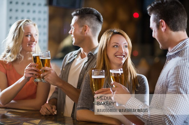 Smiling friends toasting glasses of beer in bar
